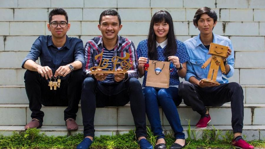 Photo of four Indonesian students sitting on a bench holding souvenirs