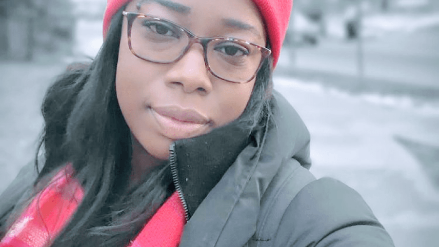 Meshanda Phillips smiles softly at the camera, wearing a pink hat and scarf and puffy jacket on a winter sidewalk