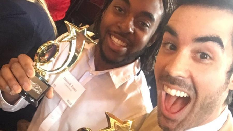 Two men smiling and holding awards