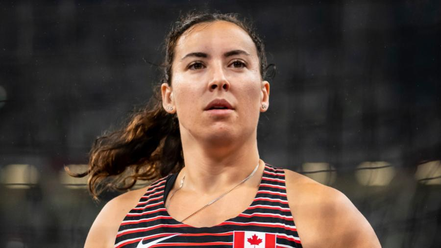 Renee Foessel looks into the distance with a shotput in her hand with stadium seats in the background.