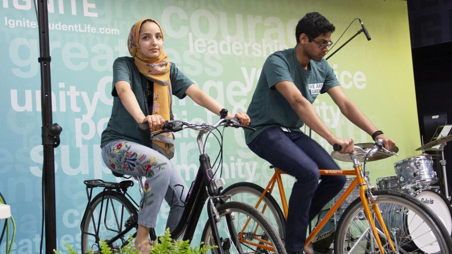 Office of Sustainability staff members cycle to provide power for the event's house band