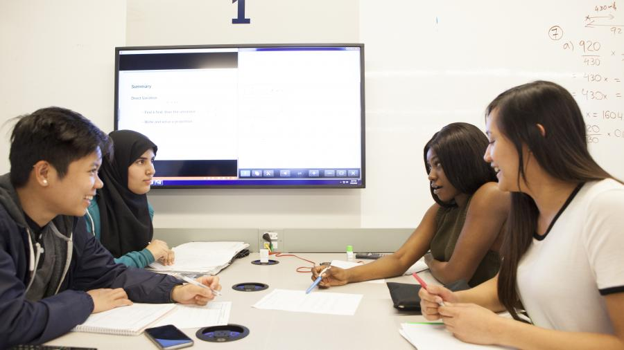 A group of students view a large screen while seated at a large table.