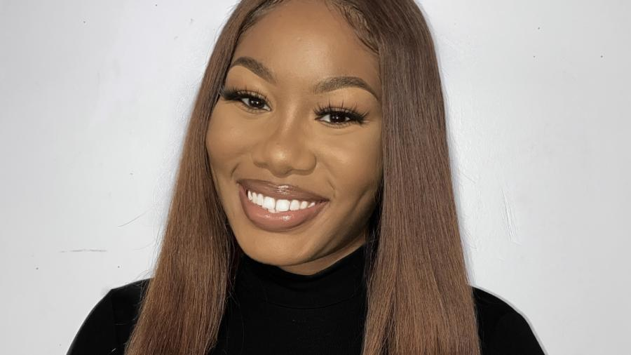 Ashley Bello smiles in front of a white background. She has long brown hair and is wearing a black turtleneck sweater