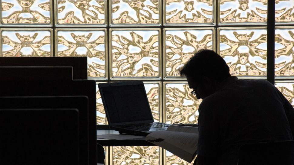 A person sits at a table working on a laptop. They are hunched and outlined in shadow in front of a glass wall.