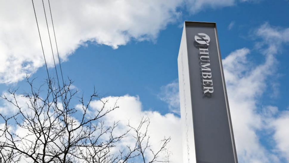 A tall pillar in front of Humber's Centre for Justice Leadership's is seen from below, against a cloudy sky, blue sky