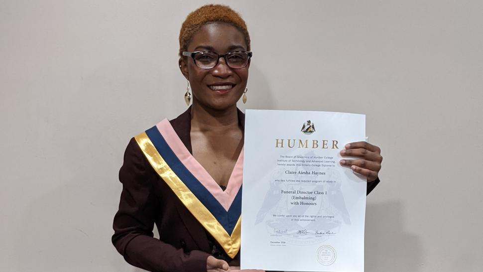Claire Doyle holds her diploma in front of her wearing a plum-coloured suit and a convocation collar