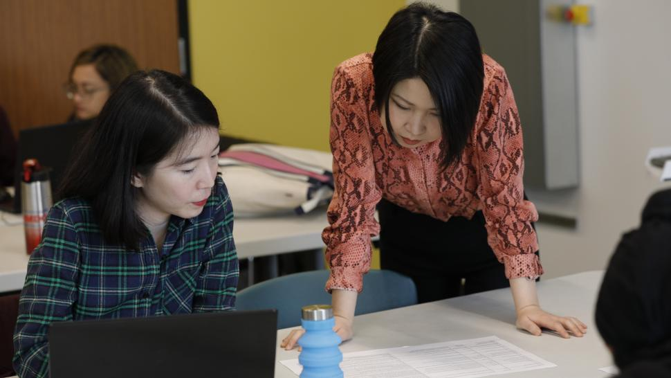 Io Qiu (right) consults with a classmate during the 2020 Siemens-Humber Hackathon