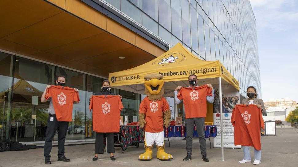 Five people stand outside of a large building, holding up orange shirts.