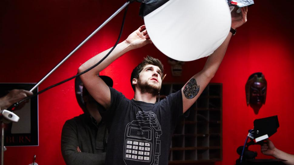 A young man holds a large, round, white set light over his head, shining into a red-walled studio.