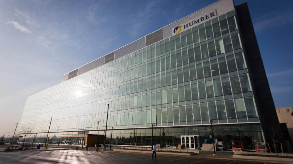 The Humber College Learning Resource Commons, which has a metal and glass facade. The sun is shining dramatically on it