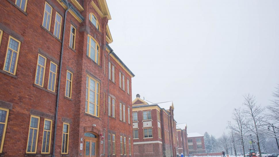 A brick building is shot from below against a grey sky with snow and bare trees