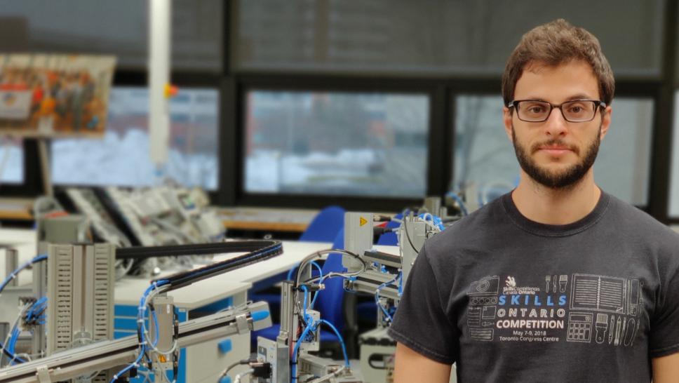 Mauricio Toigo stands in a lab at the Barrett CTI with machinery behind him. He is wearing a t-shirt, jeans and glasses