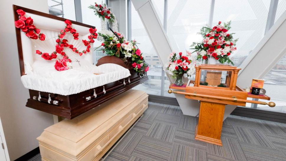An open wood casket with soft white lining sits on a stand in front of a flower-covered altar in the funeral services lab