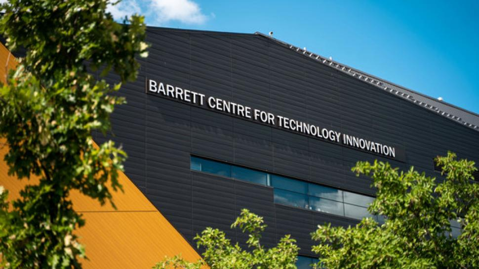 The Barrett CTI building, which is dark grey with yellow accents, shot from below in front of a blue sky