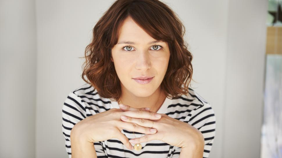 Allison Hogg smirks at the camera with her hands clasped under her chin. She's wearing a striped shirt and has brown hair