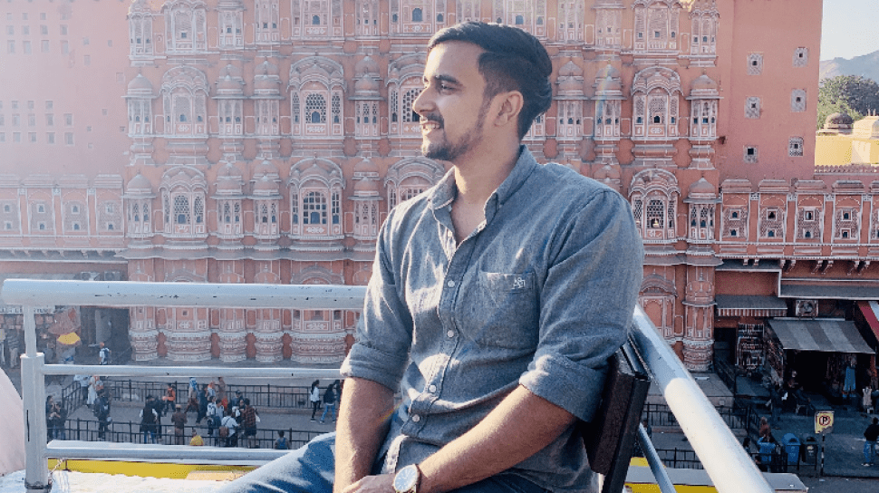 Kanishk Bhuria is seated, looking over his right shoulder with a smile, an old building with a beautiful facade in the backgrogr