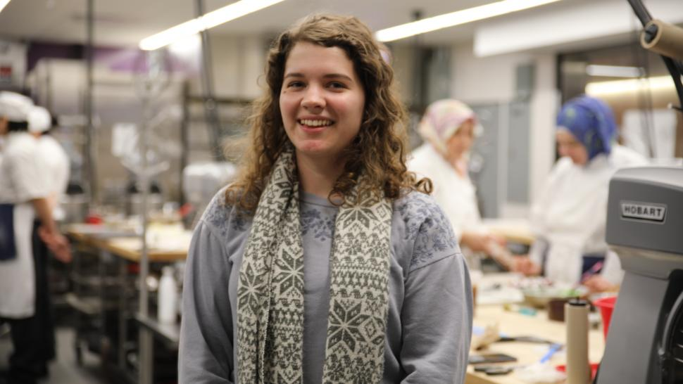 Stefanie Francavilla stands in the middle of a culinary lab at Humber with her arms crossed. She is smiling.