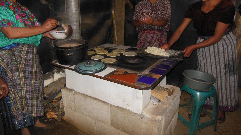 Women cook on a cement stove