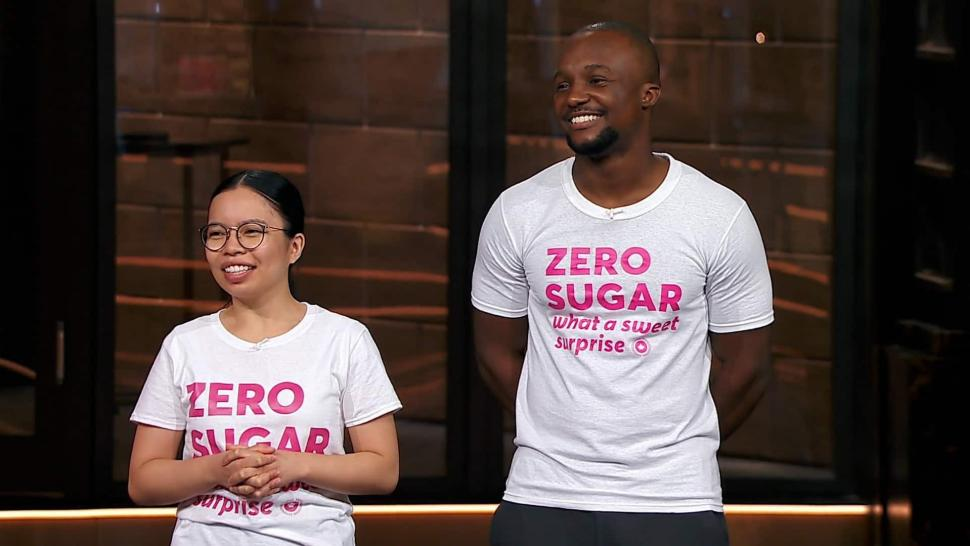 The Ambursleys on the set of Dragon's Den. They are smiling and wearing white t-shirts with the pink Oat Canada logo