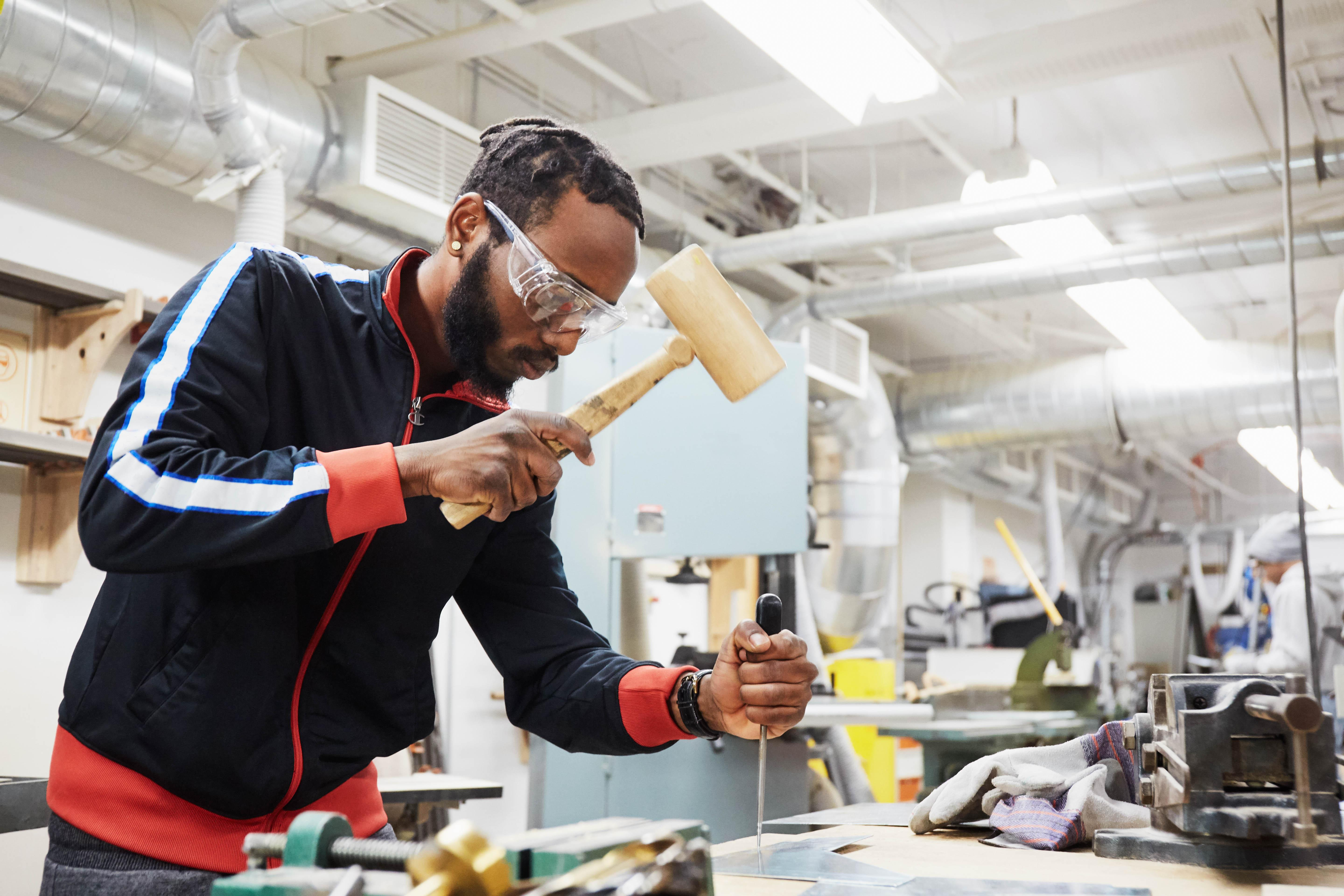 a student wearing safety goggles uses a mallet on a board in the Centre for Skilled Trades and Technology