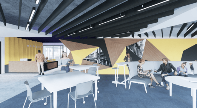 An open study space Humber's IGS building has a help desk and white study tables scattered throughout under a sloped ceiling