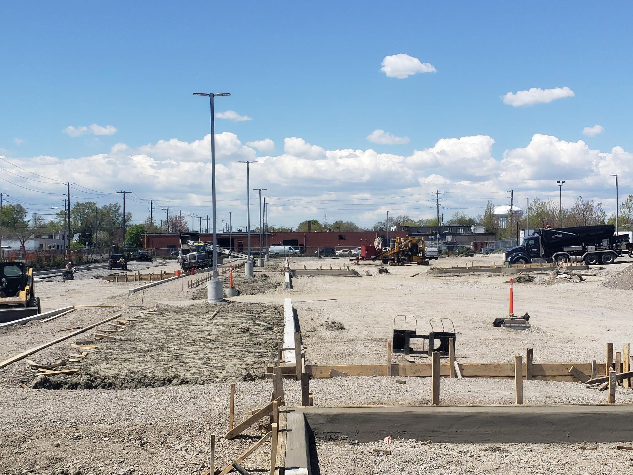 A huge parking lot is under construction. Sand covers the ground before the asphalt comes in. Big trucks pepper the property