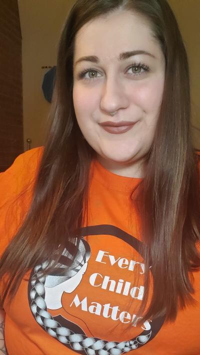 NahanneeSchuitemaker with long brown hair is wearing an orange shirt.