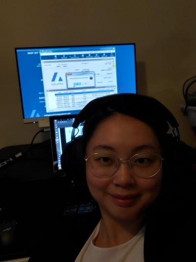 Heather Cui is wearing headphones in front of a monitor showing Applied Systems' technology