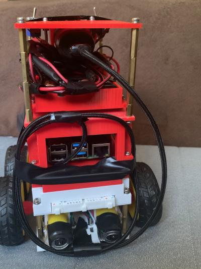 Daneep Lahs robot is red with black wires coming out of it. It is on wheels.