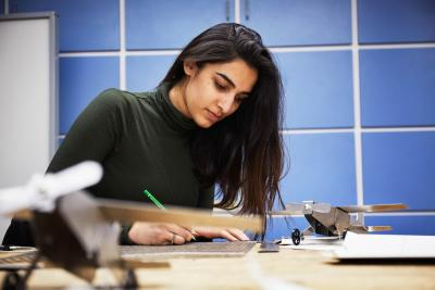 a young woman works on a project at Humber College, alone at a lab desk.