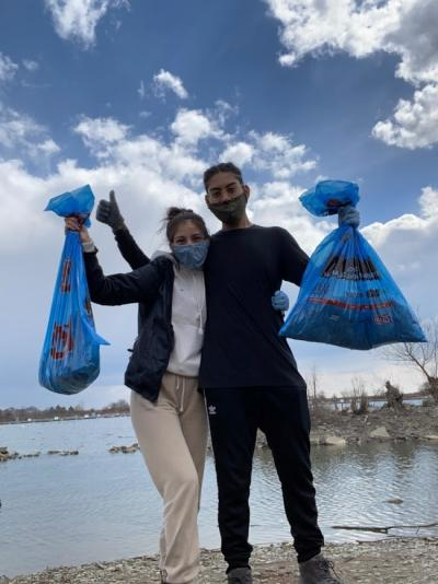 Andrea Veliz Verastegui and her friend have an arm around each others' shoulders, other hands holding blue trash bags