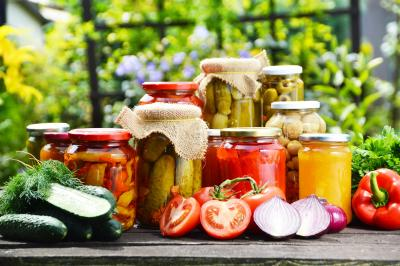 Jars of preserves on a table surrounded by colourful vegetables