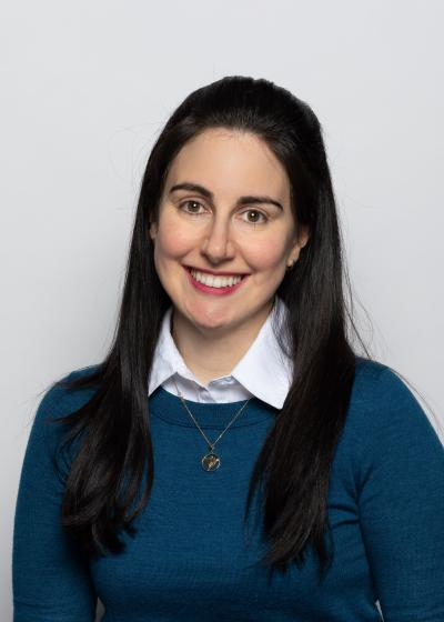 Program coordinator Erin Mandel-Shorser smiles in a headshot, wearing a collared shirt and green sweater in front of a white wal