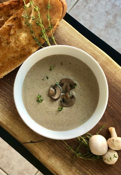 A bowl of mushroom soup sits on a cutting board beside bread and raw mushrooms. It is light brown, topped with brown mushrooms