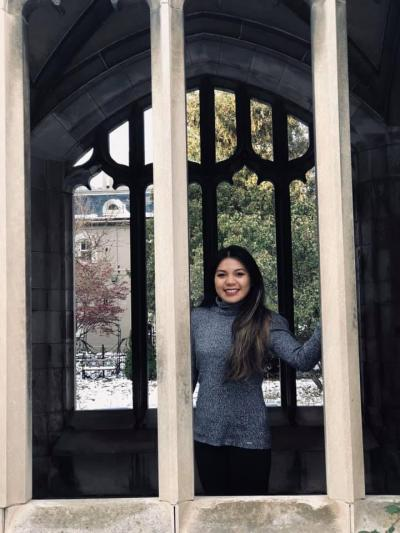 Joanne Cerdan looks out between two pillars from inside a pavillion, smiling.She is wearing a turtleneck and has long brown hair