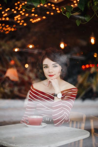 Laura Anglade is seen through a window at a coffee shop, posed in front of a cup and saucer with her hand under her chin