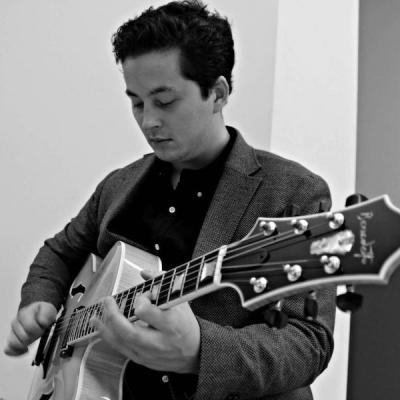 Lucian Gray is standing, wearing a blazer while playing guitar in a black and white photo.
