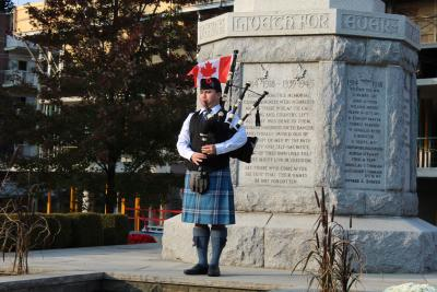 Mathias Ho plays bagpipes at the Port Credit Cenotaph. He is wearing a tartan kilt.