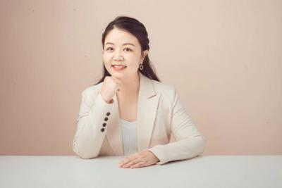 Nancy Huang sits behind a desk smiling with her chin resting on her hand. She has long black hair.