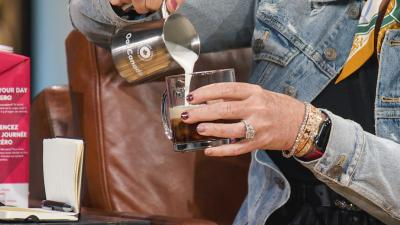 Someone is pouring oat milk from a stainless steel container into a cup. Their hands are visible and they are wearing rings