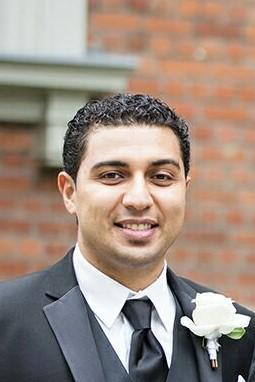 Sam Abidir smiles, wearing a formal suit with a white boutonniere. He is in front of a brick wall.