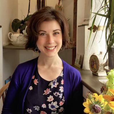 Rebecca Fitzgerald smiles widely, seated beside a window ledge surrounded by houseplants
