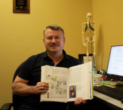 Professor Ron Stewart sits at his desk holding open a science textbook with a skeleton model in the background