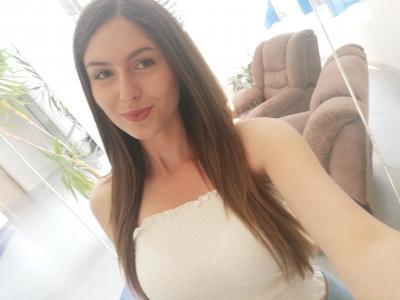 AleksandraPeychinova smiles, closemouthed, wearing a white tank top in a selfie. She has long brown hair.