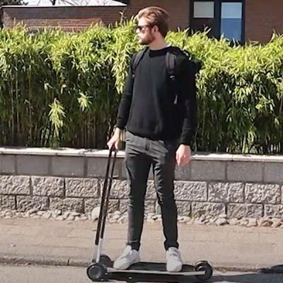 Henry Boy rides his project, Vagabond, which looks like a black electric scooter. He's sideways like on a skateboard