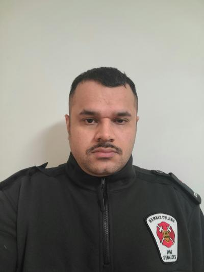 Munir Raza is wearing a black jacket with a firefighter's patch on the left breast. He is straight-faced and has a dark moustach