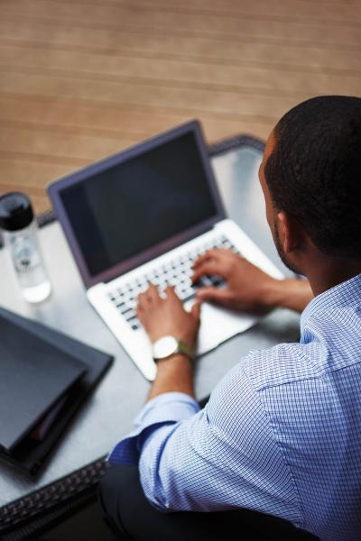 A person is seen from behind, sitting at a computer. The screen is visible over their shoulder and they are typing.