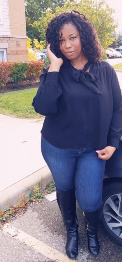 Meshanda Ellison poses in front of a car wearing jeans and a black shirt. Her hand is touching her curls softly