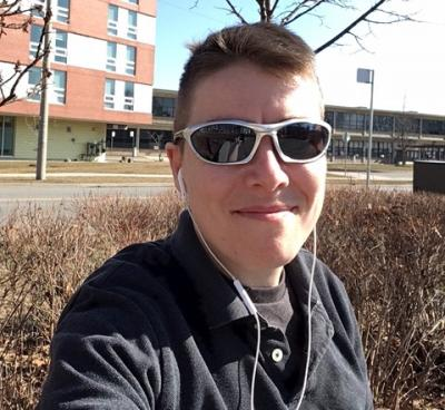 D Merkley takes a selfie across the street from a residence building at Humber's Lakeshore campus, wearing sunglasses