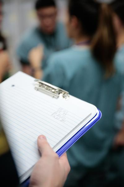 a professor takes notes as paramedic students practice skills